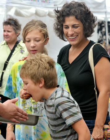 WARREN DILLAWAY / Star Beacon<br /> ISAAC RIDDELL, 8, of Ashtabula grabs a sample under the watchful eye of his mother Astel Tomasio and his sister Amelia Riddell during the Wine and Walleye Festival in Ashtabula on Saturday.