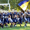 WARREN DILLAWAY / Star Beacon<br /> BRIAN DURIS (63) carries the Conneaut flag on Friday night to kick off the 2014 football season at Conneaut Stadium..