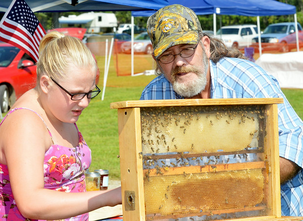 WARREN DILLAWAY / Star Beacon<br /> TOM BURRIS of Kingsville Township shows a wooden case of bees to Abriel Rood, 10, of Dorset Township during the 124th Pierpont Picnic on Saturday on Middle Road in Pierpont Township.