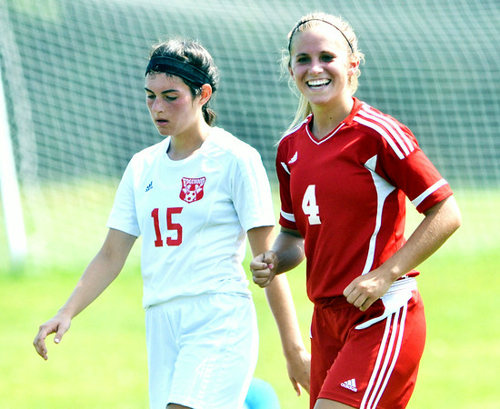 WARREN DILLAWAY / Star Beacon<br /> SUMMER ARNDT (4) of Geneva was all smiles after scoring a goal on Saturday at Edgewood as Warrior Sarah Stell (15) walks back up the field.