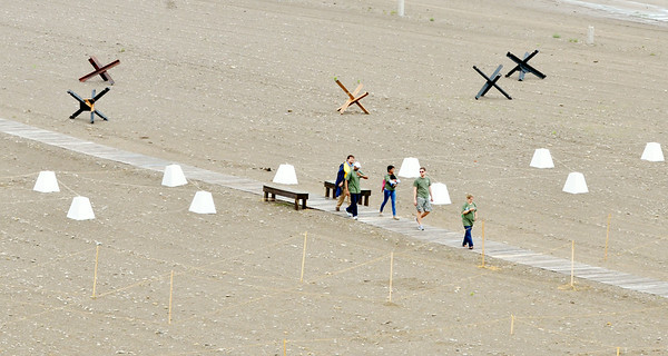 WARREN DILLAWAY / Star Beacon<br /> VISITORS TO D-Day Conneaut walk the Conneaut Township Park boardwalk amidst invasion equipment on Friday morning.