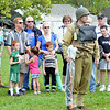 WARREN DILLAWAY / Star Beacon<br /> PRIVATE BRITTON WILLIAMS (center facing) displays World War II era uniforms with Lt. Paul Veneziano (right) as visitors to D-Day Conneaut look on on Friday at Conneaut Township Park.