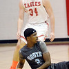 WARREN DILLAWAY / Star Beacon<br /> SETH CALHOUN (34) of Geneva defends Doug Burks of Willoughby South who dove to the court on Friday night during a game at Geneva.