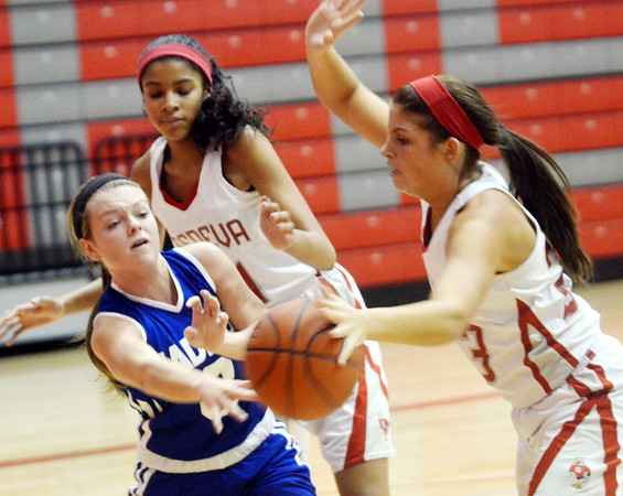 WARREN DILLAWAY / Star Beacon<br /> ABBIE THOMPSON (left) of Madison tries to pass the ball to a teammate while Sarah Juncker (right) and Geneva teammate Hailey Peoples (back left) defend on Saturday afternoon in Geneva.