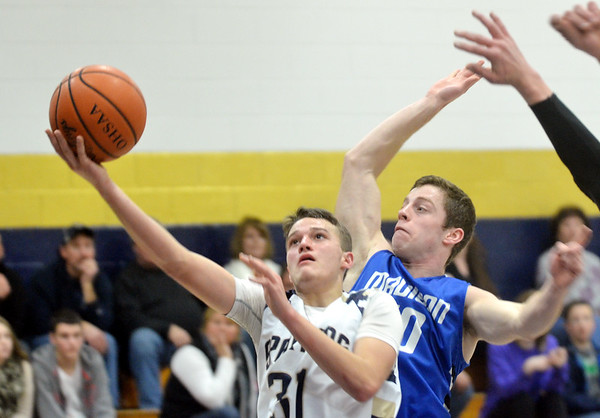 WARREN DILLAWAY / Star Beacon<br /> JUSTIN MYERS (31) of Conneaut drives to the basket in front of Aaron Petrucelli of Madison on Saturday night at Garcia Gymnasium in Conneaut.