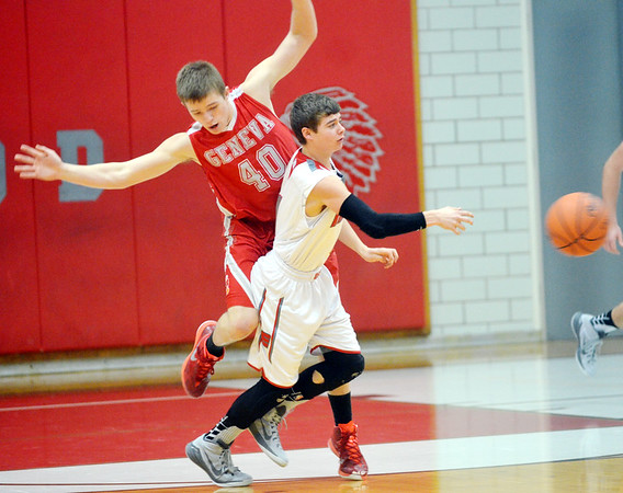 WARREN DILLAWAY / Star Beacon<br /> MITCHELL DRAGON of Edgewood passes to a teammate as Ryan Mackynen of Geneva (40) attempts to avoid contact on Saturday evening at Edgewood.