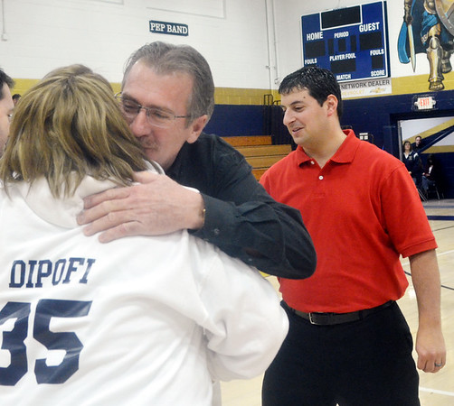 WARREN DILLAWAY / Star Beacon<br /> GREG SWEET, owner of Greg Sweet Chevrolet-Buick, (facing) hugs Conneaut Area City Schools School Board Member Diana DiPofi  as school board president Chris Newcomb looks on (right) on Tuesday evening during a ceremony to honor Sweet's donation of two scoreboards to Garcia Gymnasium.
