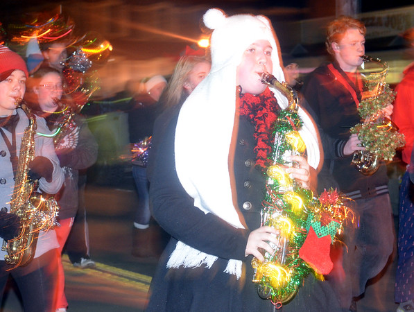 WARREN DILLAWAY / Star Beacon<br /> AMANDA  ROMBAUGH (in white hat) plays the saxophone in the Jefferson High School band on Saturday night during the Jefferson Christmas Parade.
