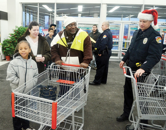 WARREN DILLAWAY / Star Beacon<br /> CONNEAUT POLICE Officer John Helfer (right) assists Maurice Williams-Laird (front left), 7, and Diane and Ben Williams-Laird during the Conneaut Shop with an Officer program at the Super KMart in Ashtabula Township on Saturday morning.