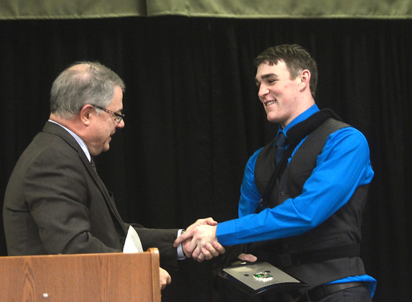 WARREN DILLAWAY / Star Beacon<br /> AUSTIN CLUTTER, a senior at Geneva High School, (right) receives the Warren G. Andrews Memorial Scholarship Award from Mark Andrews on Monday night during the Ashtabula County Touchdown Club Banquet at Our Lady of Peace Community Center in Ashtabula.
