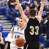 WARREN DILLAWAY / Star Beacon<br /> MATT LARNED (12) of Grand Valley drives to the basket as Dakota Harmotta of Windham defends on Friday evening in Orwell during opening night basketball action.