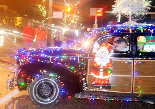 WARREN DILLAWAY / Star Beacon<br /> BRIGHT CHRISTMAS lights lit up an antique car and downtown Geneva on Friday night during the city's Christmas parade.