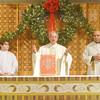 WARREN DILLAWAY / Star Beacon<br /> REV. RAYMOND THOMAS (center arms raised) leads a Christmas Mass at Our Lady of Peace Parish Mount Carmel in Ashtabula on Thursday morning.