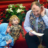WARREN DILLAWAY / Star Beacon<br /> REV. PETER NIELSEN gestures during the presentation of the Christmas story to a group of people including Carter Cline, 4, and his brother  Jasper (standing) , both of Kingsville Township, during a Christmas Day service at St. Peter's Episcopal Church in Ashtabula on Thursday morning.