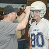 WARREN DILLAWAY / Star Beacon<br /> JOE BENTO, an assisstant football coach at St. John, adjusts the helmet of his son Ryan Bento, an eighth grader, during the first day of practice at Massucci Field in Ashtabula.