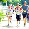 WARREN DILLAWAY / Star Beacon<br /> ERIC CORNELIUS (right) and Chrissy Falloon (center) run with Eric's mother Valerie Silleck (left) at the end of the Ashtabula YMCA Firecracker 5k on Friday.