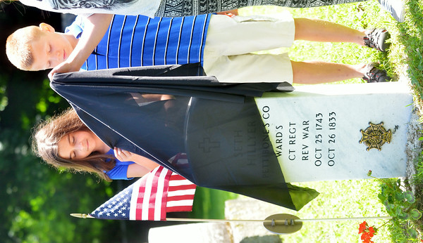 WARREN DILLAWAY / Star Beacon<br /> MAGGIE STASIAK (left) and Andrew Root unveil a new tombstone for distant relative Seth Hillyer who served in the Revolutionary War. The ceremony was sponsored by the Northeast Ohio Chapter of the Sons of the American Revolution and held at Andover Congregational Church Cemetery.