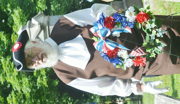 WARREN DILLAWAY / Star Beacon<br /> MEMBERS OF the Northeastern Ohio Chapter of the Sons of the American Revolutionary War led a grave marking ceremony for Revolutionary War veterans at four Ashtabula County ceremonies on Friday. Don Taft carries a wreath to the grave of John Pickett.