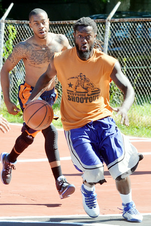 WARREN DILLAWAY / Star Beacon<br /> PHENO KING of Thirsty Bird drives to the basket with Lavell Stevens following the play on Saturday morning during the West Side Shoot Out in Ashtabula.