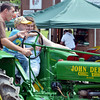 WARREN DILLAWAY / Star Beacon<br /> EAN SMITH, 6, of Garretsville, gets some driving help from Matt and Julie Barker of Kinsman during a parade at the Ashtabula County Antique Engine Club Show in Wayne Township on Saturday.