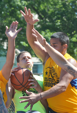 WARREN DILLAWAY / Star Beacon<br /> RAY HENTON of Staff drives to the basket with Carlos Cancel of Steve's Car Wash (right) defending following the play on Saturday morning during the West Side Shoot Out in Ashtabula.