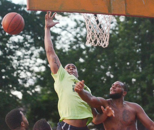 WARREN DILLAWAY / Star Beacon<br /> GEOVANTE ROSE of Chick's Bar loses the ball as Rayshawn Journigan of Rex Inc. defends on Saturday during the West Side Shootout championship game in Ashtabula.
