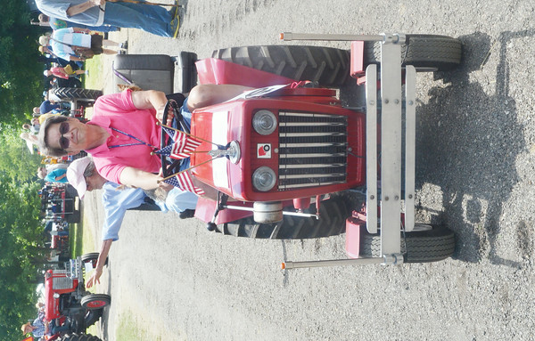 WARREN DILLAWAY / Star Beacon<br /> MARTI SHAFFER of New Springfield drives a tractor during a parade at the Ashtabula County Antique Engine Club Show in Wayne Township on Saturday.