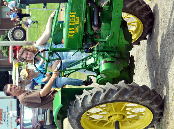 WARREN DILLAWAY / Star Beacon<br /> EAN SMITH, 6, of Garretsville, gets some driving help from Matt and Julie Barker of Kinsman during a parade at the Ashtabula County Engine Club Show in Wayne Township on Saturday.