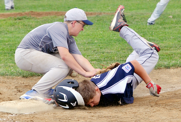 WARREN DILLAWAY / Star Beacon<br /> RICHARD PICARD of Conneaut loses his helmet while sliding safely back into third base with David Nye of Grand Valley applying the tag on Monday evening at Skippon Park in Conneaut.