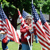 MARTHA TESSMER of Conneaut claims her flag following the closing ceremony of the Fields of Honor on Saturday in North Kingsville's Greenlawn Memory Gardens. She sponsored the flag in honor of her father James Clancy who served during World War II and passed away last year.