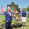 WARREN DILLAWAY / Star Beacon<br /> DIANNA KUNDAS, president of the Garden Trails Garden Club, (right) and Kathy Michney, president of the Blue Star Mothers Chapter 57, pose after placing a wreath during a Blue Star Memorial dedication on Saturday afternoon at Lake Shore Park in Ashtabula Township.