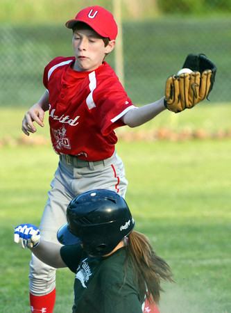 WARREN DILLAWAY / Star Beacon<br /> EMMA GURLEY of Painesville slides safely in to second base as Alex Bryan of United grabs a late throw during Junior League action at Kiwanis Park in Geneva on Monday evening.
