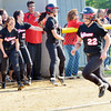 WARREN DILLAWAY / Star Beacon<br /> TAYLOR JOHNSTON (12) of Jefferson cheers for Deanna Comp (22) as she prepares to score the winning run on Thursday during a Division II district semifinal at the Jefferson Area Girls Softball complex.