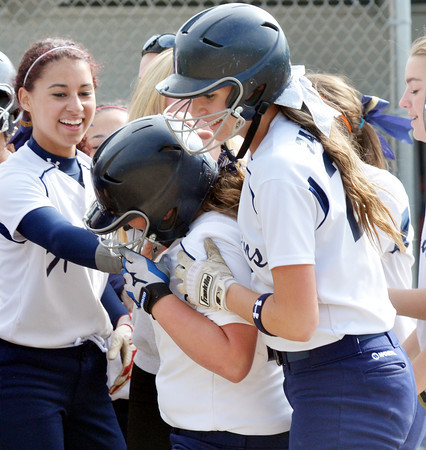 WARREN DILLAWAY / Star Beacon<br /> ALEXIS NELSON of Conneaut (center) gets mobbed by teammates Amanda Chadwick (left) and Lex Zappitelli (right) on Thursday during a Division II district semifinal at the Jefferson Area Girls Softball Complex.