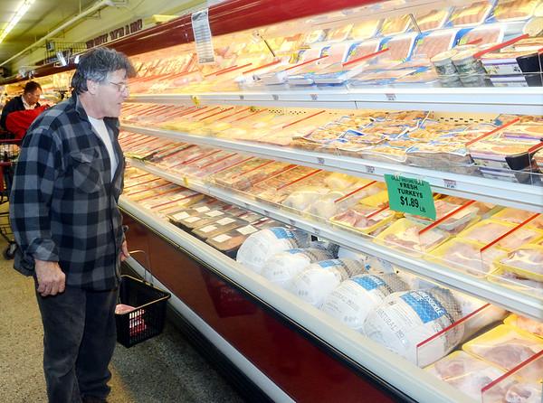 WARREN DILLAWAY / Star Beacon<br /> BOB STRANMAN of Conneaut checks out the turkey section at Orlando's Golden Dawn in Conneaut on Monday.