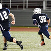 WARREN DILLAWAY / Star Beacon<br /> JOSH STOLL (12) of St. John leads the blocking for teammate James Woods (32) on Friday night during a game with Toronto at Spire Institute in Harpersfield Township.