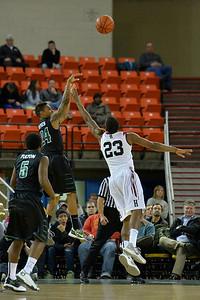 November 29, 2013: Green Bay Phoenix guard Keifer Sykes (24) shoots a three over Harvard Crimson guard/forward Wesley Saunders (23) in a semifinal game at the 2013 Great Alaska Shootout between Harvard and Green Bay. Harvard defeated Green Bay 76-64.