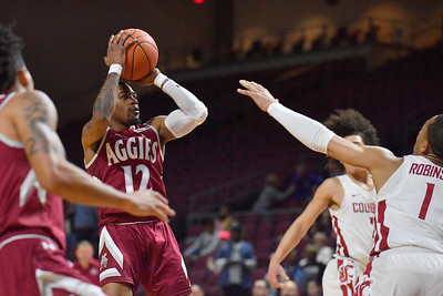 LAS VEGAS, NV - DECEMBER 23:  AJ Harris #12 of the New Mexico State Aggies shoots against Jervae Robinson #1 of the Washington State Cougars during the consolation game of the Continental Tire Las Vegas Classic at the Orleans Arena in Las Vegas, Nevada.  (Photo by Sam Wasson for NM State Athletics)