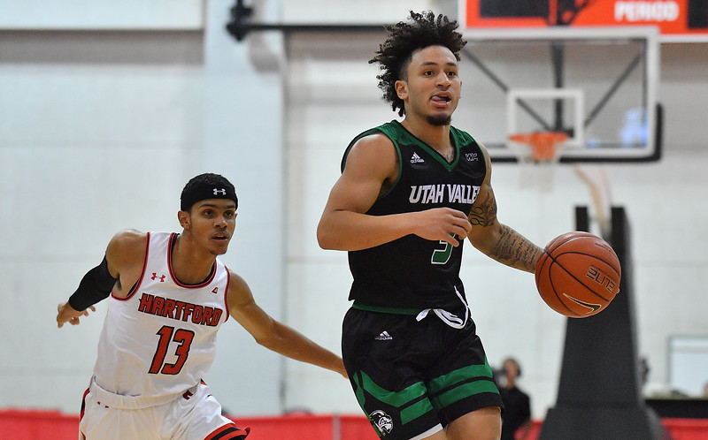 LAS VEGAS, NV - NOVEMBER 19:  TJ Washington #3 of the Utah Valley Wolverines drives past J.R. Lynch #13 of the Hartford Hawks during their middleweight bracket semifinal game of the MGM Resorts Main Event at Cox Pavilion in Las Vegas, Nevada.  (Photo by Sam Wasson for Utah Valley Athletics)