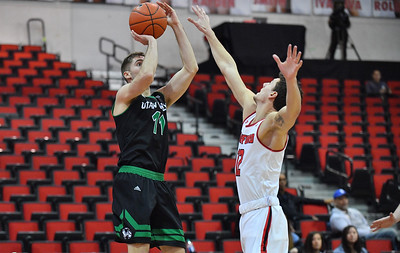LAS VEGAS, NV - NOVEMBER 19:  Conner Toolson #11 of the Utah Valley Wolverines shoots against Jason Dunne #12 of the Hartford Hawks during their middleweight bracket semifinal game of the MGM Resorts Main Event at Cox Pavilion in Las Vegas, Nevada. Utah Valley defeated Hartford 72-65.  (Photo by Sam Wasson for Utah Valley Athletics)