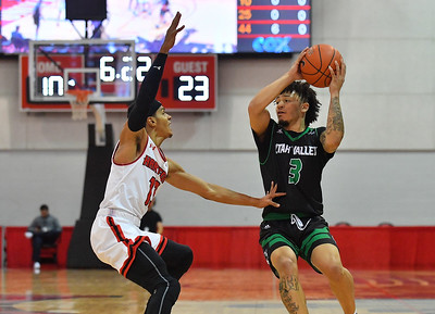 LAS VEGAS, NV - NOVEMBER 19:  TJ Washington #3 of the Utah Valley Wolverines drives against J.R. Lynch #13 of the Hartford Hawks during their middleweight bracket semifinal game of the MGM Resorts Main Event at Cox Pavilion in Las Vegas, Nevada.  (Photo by Sam Wasson for Utah Valley Athletics)
