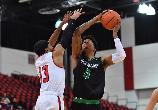 LAS VEGAS, NV - NOVEMBER 19:  Isaiah White #0 of the Utah Valley Wolverines shoots against J.R. Lynch #13 of the Hartford Hawks during their middleweight bracket semifinal game of the MGM Resorts Main Event at Cox Pavilion in Las Vegas, Nevada.  (Photo by Sam Wasson for Utah Valley Athletics)