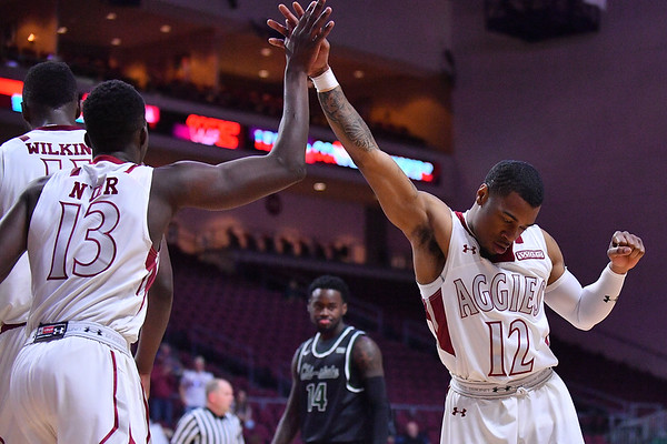 LAS VEGAS, NV - MARCH 08:  Sidy N'Dir #13 of the New Mexico State Aggies high-fives teammate A.J. Harris #12 after converting a layup against the Chicago State Cougars during a quarterfinal game of the Western Athletic Conference basketball tournament at the Orleans Arena in Las Vegas, Nevada. The Aggies won 97-70.