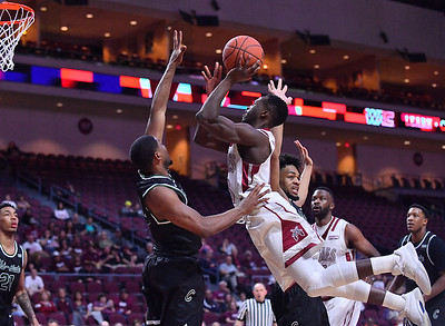 LAS VEGAS, NV - MARCH 08:  Sidy N'Dir #13 of the New Mexico State Aggies shoots against Glen Burns (L) #0 and Deionte Simmons #3 of the Chicago State Cougars during a quarterfinal game of the Western Athletic Conference basketball tournament at the Orleans Arena in Las Vegas, Nevada. The Aggies won 97-70.