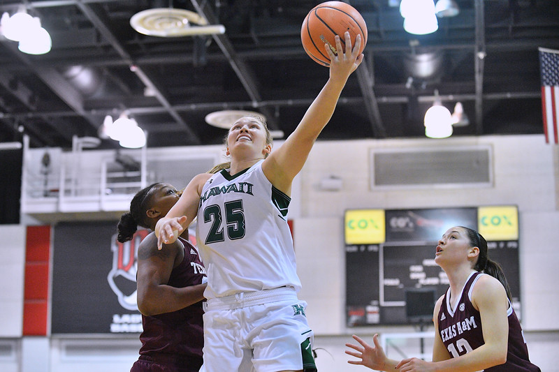 Dec 20, 2017; Las Vegas, NV, USA;  Hawai'i Rainbow Wahine forward Amy Atwell (25) drives in for a layup against Texas A&M Aggies forward Caylinne Martin (34) during the Duel In The Desert at the Cox Pavilion in Las Vegas, Nevada.  Photo by Sam Wasson for Hawai'i Athletics