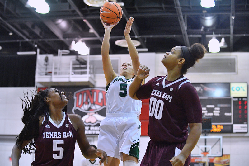 Dec 20, 2017; Las Vegas, NV, USA;  Hawaii Rainbow Wahine guard Sarah Toeaina #5 shoots against Texas A&M Aggies forward Anriel Howard #5 and Texas A&M Aggies center Khaalia Hillsman #00 during the Duel In The Desert at the Cox Pavilion in Las Vegas, Nevada.  Photo by Sam Wasson for Hawai'i Athletics