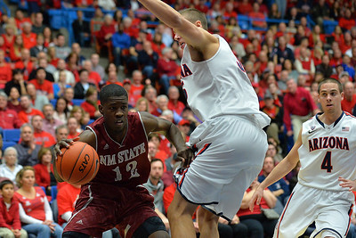 December 11, 2013: New Mexico State Aggies guard K.C. Ross-Miller (12) drives past Arizona Wildcats center Kaleb Tarczewski (35) in a game between No. 1 Arizona and New Mexico State at McKale Center in Tucson, Ariz. Arizona defeated New Mexico State 74-48.