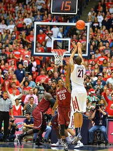 December 11, 2013: Arizona Wildcats forward Brandon Ashley (21) shoots a three pointer over New Mexico State Aggies guard Daniel Mullings (23) in a game between No. 1 Arizona and New Mexico State at McKale Center in Tucson, Ariz. Arizona defeated New Mexico State 74-48.