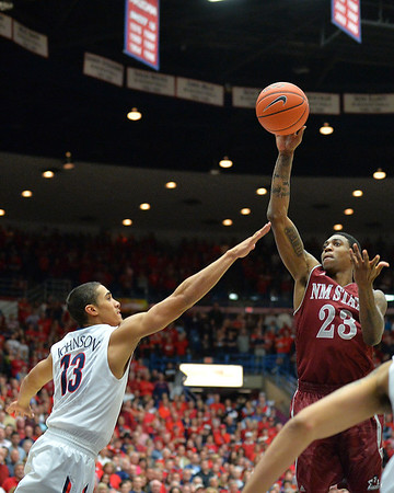 December 11, 2013: New Mexico State Aggies guard Daniel Mullings (23) shoots over Arizona Wildcats guard Nick Johnson (13) in a game between No. 1 Arizona and New Mexico State at McKale Center in Tucson, Ariz. Arizona defeated New Mexico State 74-48.