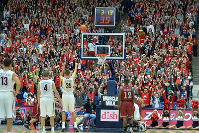 December 11, 2013: The Arizona Wildcats Zona Zoo student section raise their arms as Arizona Wildcats center Kaleb Tarczewski (35) shoots a free throw in a game between No. 1 Arizona and New Mexico State at McKale Center in Tucson, Ariz. Arizona defeated New Mexico State 74-48.